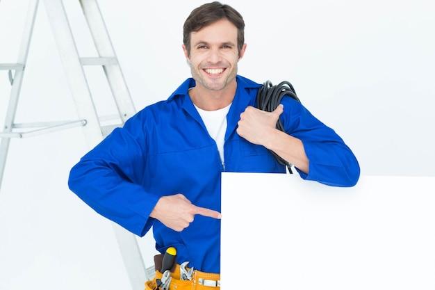 Hübscher elektriker mit dem draht, der auf anschlagbrett zeigt