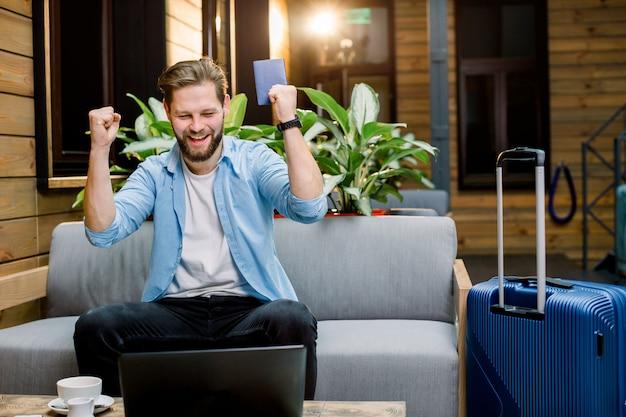 Hübscher emotionaler junger mann, der hände hoch hält, sitzt auf dem sofa mit laptop und pass in händen. vorbereitung auf reisen