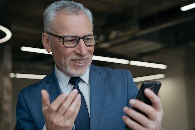 Hübscher emotionaler mann, der handy für videokonferenz verwendet, im modernen büro arbeitend