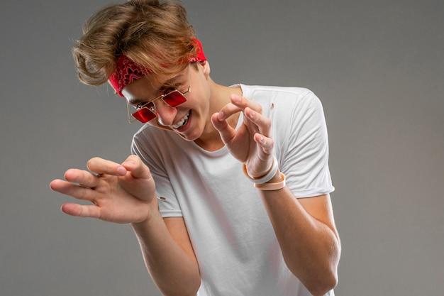Hübscher emotionaler teenagerjunge, der im studio gegen grau, kerl in einem grauen t-shirt und in der roten sonnenbrille verzieht grimassen und lacht