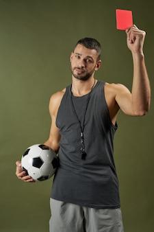 Hübscher entzückender fußballschiedsrichter, der fußballspieler im sportzentrum ausbildet
