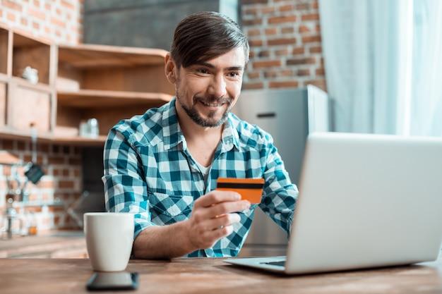 Hübscher entzückter positiver mann, der lächelt und vor dem computer sitzt, während er mit seiner kreditkarte bezahlt