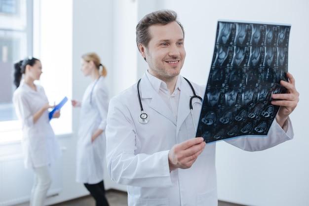 Hübscher, erfahrener, reifer chirurg, der im labor arbeitet und ein röntgenfoto hält, während seine kollegen das gespräch hinter sich genießen