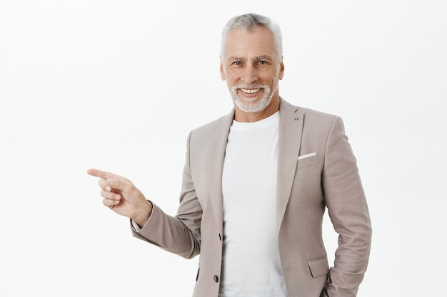 Hübscher erfolgreicher älterer geschäftsmann, der finger links zeigt