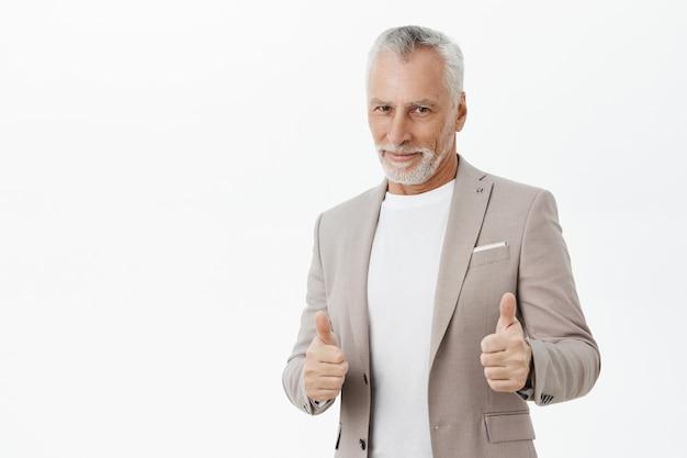 Hübscher erfolgreicher geschäftsmann, der lächelt und daumen hoch in zustimmung zeigt