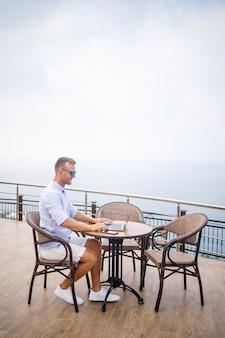 Hübscher erfolgreicher junger männlicher geschäftsmann, der an einem tisch am pool mit einem laptop mit blick auf das mittelmeer sitzt. fernarbeit im urlaub. urlaubskonzept