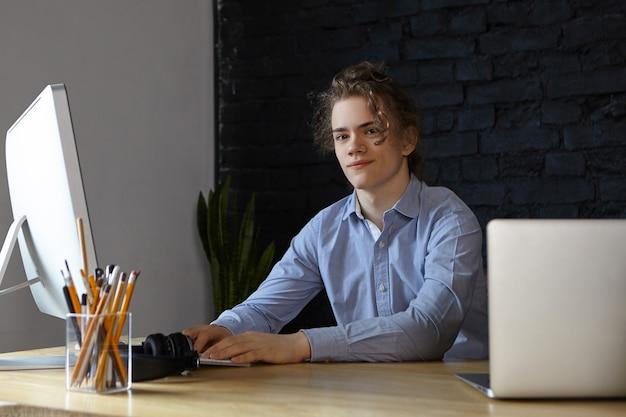 Hübscher erfolgreicher junger männlicher unternehmer, gekleidet in das lächelnde blaue hemd, das neues start-up-geschäftsprojekt an seinem arbeitsplatz entwickelt, große ideen und pläne hat, mit modernen elektronischen geräten