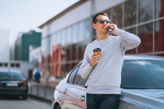 Hübscher erfolgreicher mann mit dem auto mit mobiltelefon