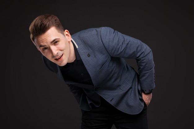 Hübscher ernster geschäftsmann in der grauen jacke, in der kostspieligen uhr und im schwarzen hemd, schwarz