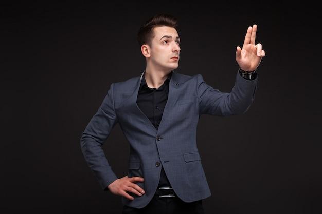 Hübscher ernster geschäftsmann in der grauen jacke, in der kostspieligen uhr und im schwarzen hemd, schwarzer hintergrund