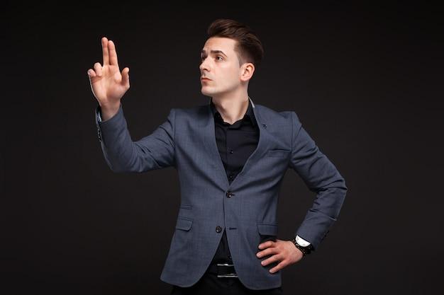 Hübscher ernster junger geschäftsmann in der grauen jacke, in der kostspieligen uhr und im schwarzen hemd