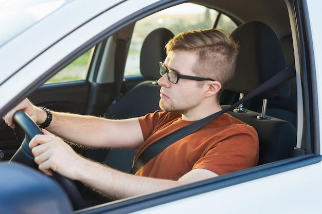 Hübscher ernster junger mann fährt ein auto.