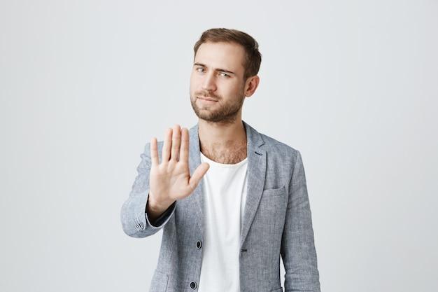 Hübscher ernsthafter mann sagen aufhören. handfläche im verbot zeigen