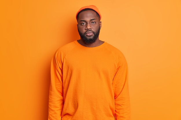 Hübscher ernsthafter ruhiger kerl mit dunkler haut und bart trägt hut lässiger pullover schaut direkt auf kameraposen gegen lebendige orange wand