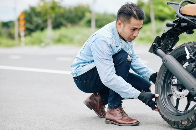 Hübscher ernsthafter vietnamesischer motorradfahrer, der reifen seines motorrads abzieht, um es aufzupumpen