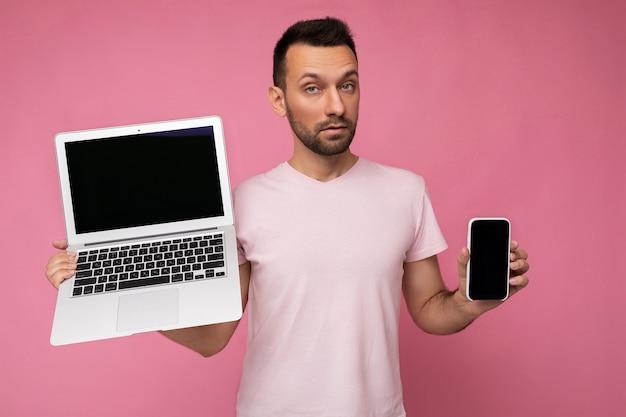 Hübscher erstaunter brunet-mann, der laptop-computer und handy hält, die kamera im t-shirt auf lokalisiertem rosa betrachten.
