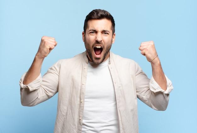 Hübscher erwachsener blonder mann, der aggressiv mit einem wütenden ausdruck oder mit geballten fäusten schreit, um den erfolg zu feiern