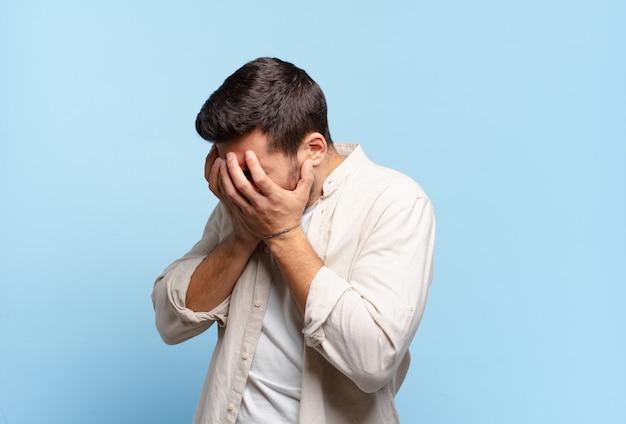 Hübscher erwachsener blonder mann, der augen mit händen mit einem traurigen, frustrierten blick der verzweiflung, des weinens, der seitenansicht bedeckt