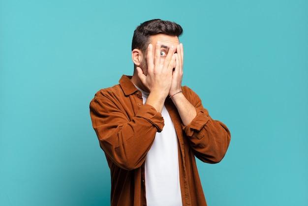 Hübscher erwachsener blonder mann, der das gesicht mit den händen bedeckt, zwischen den fingern mit überraschtem ausdruck späht und zur seite schaut