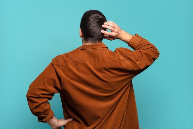 Hübscher erwachsener blonder mann, der denkt oder zweifelt, kopf kratzt, sich verwirrt und verwirrt fühlt, rück- oder rückansicht