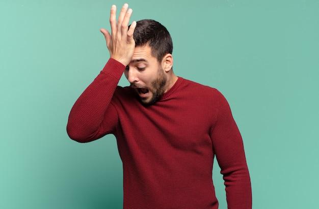 Hübscher erwachsener blonder mann, der die handfläche zur stirn hebt und denkt, oops, nachdem er einen dummen fehler gemacht oder sich daran erinnert hat, sich dumm zu fühlen?