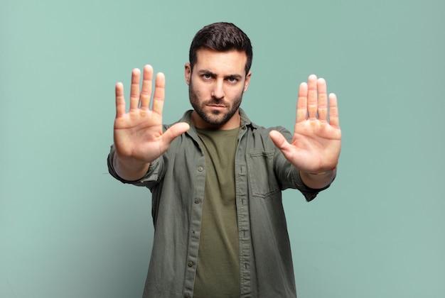 Hübscher erwachsener blonder mann, der ernst, unglücklich, wütend und unzufrieden aussieht, den eintritt zu verbieten oder zu sagen, stoppen sie mit beiden offenen handflächen