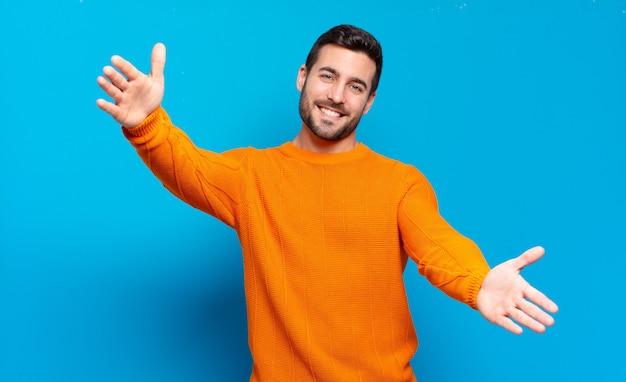 Hübscher erwachsener blonder mann, der fröhlich lächelt und eine warme, freundliche, liebevolle willkommensumarmung gibt, sich glücklich und entzückend fühlt