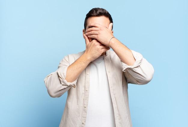 Hübscher erwachsener blonder mann, der gesicht mit beiden händen bedeckt, die nein sagen! bilder verweigern oder fotos verbieten
