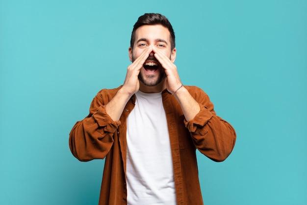 Hübscher erwachsener blonder mann, der glücklich, aufgeregt und positiv fühlt, einen großen schrei mit den händen neben dem mund gibt und ruft