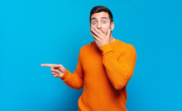 Hübscher erwachsener blonder mann, der glücklich, schockiert und überrascht fühlt, mund mit hand bedeckt und auf seitlichen kopierraum zeigt