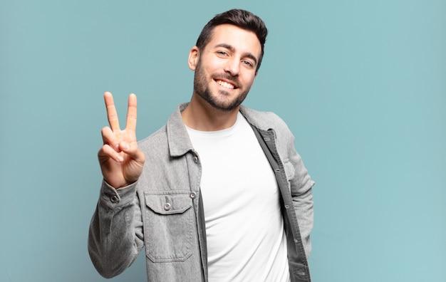 Hübscher erwachsener blonder mann, der glücklich, sorglos und positiv lächelt und aussieht und mit einer hand sieg oder frieden gestikuliert