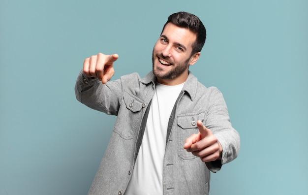 Hübscher erwachsener blonder mann, der glücklich und sicher fühlt, mit beiden händen nach vorne zeigt und lacht, sie wählt