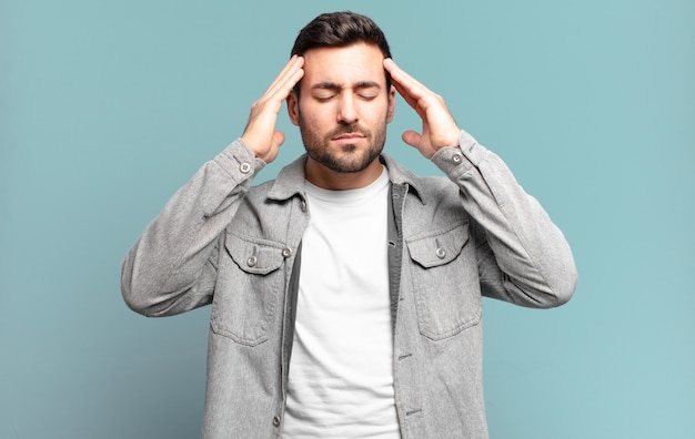 Hübscher erwachsener blonder mann, der konzentriert, nachdenklich und inspiriert aussieht, brainstorming macht und sich mit den händen auf der stirn vorstellt