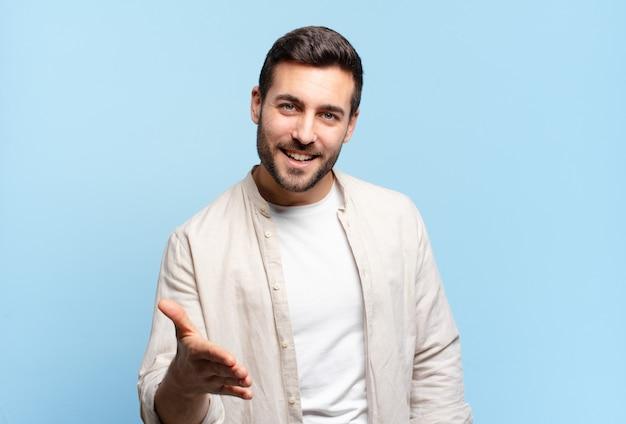 Hübscher erwachsener blonder mann, der lächelt, glücklich, selbstbewusst und freundlich aussieht, einen handschlag anbietet, um einen deal abzuschließen, kooperierend