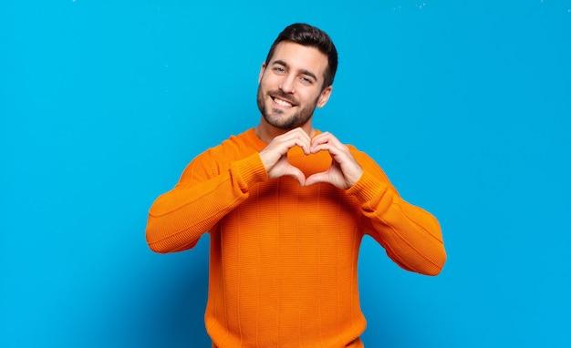 Hübscher erwachsener blonder mann, der lächelt und sich glücklich, süß, romantisch und verliebt fühlt und mit beiden händen herzform macht