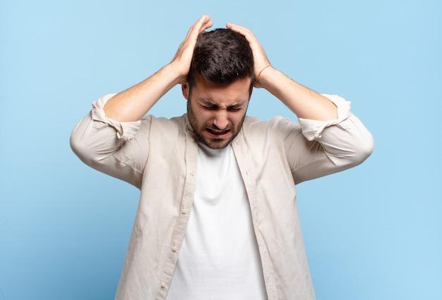 Hübscher erwachsener blonder mann, der sich gestresst und frustriert fühlt, die hände zum kopf hebt, sich müde, unglücklich und mit migräne fühlt