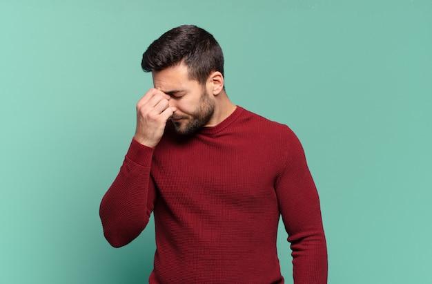 Hübscher erwachsener blonder mann, der sich gestresst, unglücklich und frustriert fühlt, die stirn berührt und unter migräne mit starken kopfschmerzen leidet