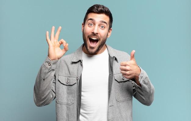 Hübscher erwachsener blonder mann, der sich glücklich, erstaunt, zufrieden und überrascht fühlt, in ordnung zeigt und gesten mit dem daumen nach oben zeigt, lächelt