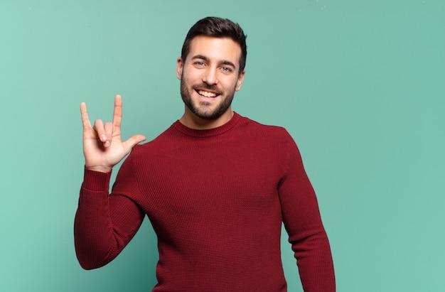 Hübscher erwachsener blonder mann, der sich glücklich, lustig, selbstbewusst, positiv und rebellisch fühlt und mit der hand rock- oder heavy-metal-schilder macht