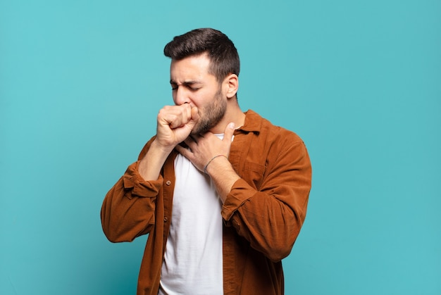 Hübscher erwachsener blonder mann, der sich mit halsschmerzen und grippesymptomen krank fühlt und mit bedecktem mund hustet