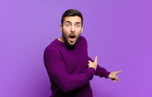 Hübscher erwachsener blonder mann, der sich schockiert und überrascht fühlt und auf den kopierraum auf der seite mit erstauntem, offenem mund zeigt