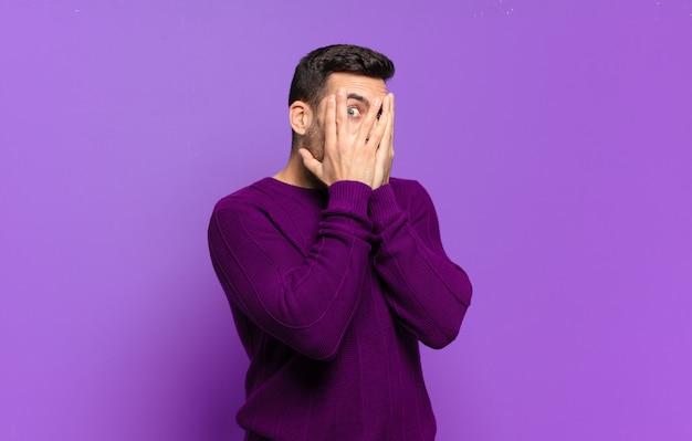 Hübscher erwachsener blonder mann, der sich verängstigt oder verlegen fühlt, mit halb mit händen bedeckten augen späht oder ausspioniert
