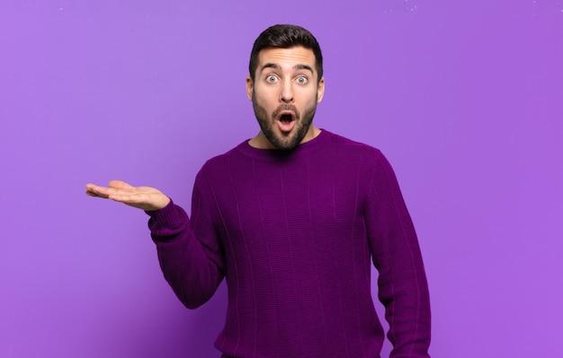Hübscher erwachsener blonder mann, der überrascht und geschockt aussieht, mit gesenktem kiefer, der einen gegenstand mit einer offenen hand auf der seite hält