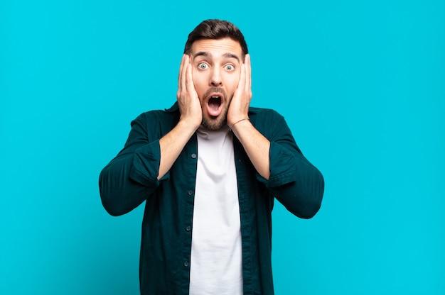 Hübscher erwachsener blonder mann, der unangenehm geschockt, verängstigt oder besorgt aussieht, mund weit offen und beide ohren mit händen bedeckend