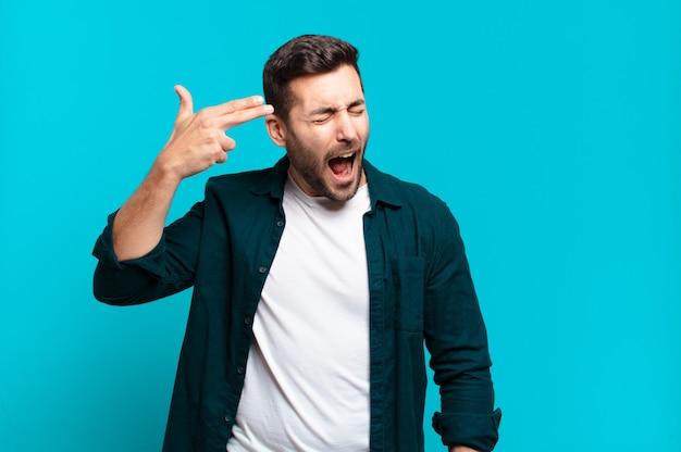 Hübscher erwachsener blonder mann, der unglücklich und gestresst aussieht, selbstmordgeste, die waffenzeichen mit hand macht, zeigt auf kopf