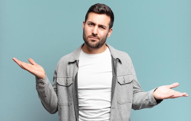 Hübscher erwachsener blonder mann, der verwirrt, verwirrt und gestresst aussieht, sich zwischen verschiedenen optionen wundert und sich unsicher fühlt