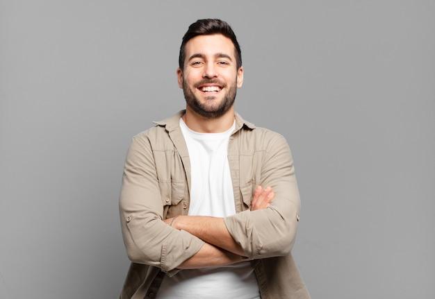 Hübscher erwachsener blonder mann, der wie ein glücklicher, stolzer und zufriedener leistungsträger aussieht, der mit verschränkten armen lächelt