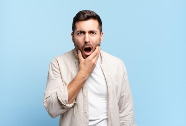 Hübscher erwachsener blonder mann mit weit geöffnetem mund und augen und hand am kinn, der sich unangenehm schockiert fühlt und sagt, was oder wow