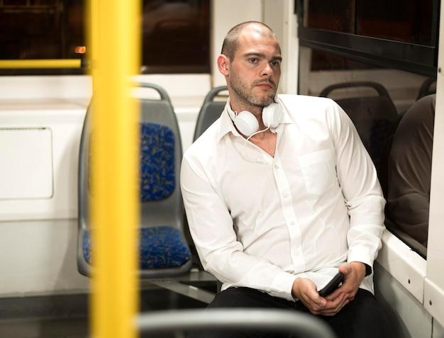 Hübscher erwachsener mann, der den bus reitet