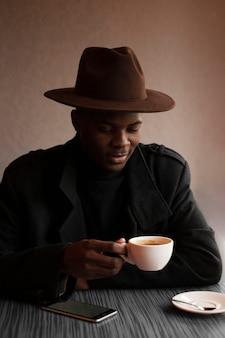 Hübscher erwachsener mann, der eine tasse tee genießt